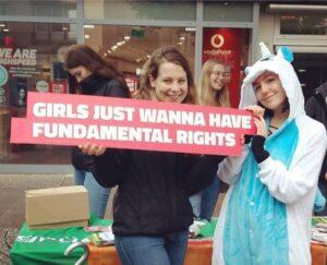 """zwei Mädchen mit Einhornkostüm und einem Schild mit der Aufschrift """"Girls just wanna have fundamental rights"""""""