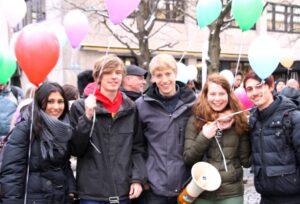 5 junge Menschen mit Luftballons und Mikrophon auf einer Demonstration