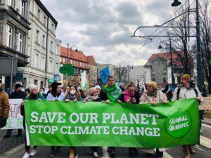 "Grüne demonstrieren hinter dem Banner ""Save our Planet, stop climate change"""