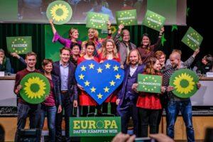 Grünen Politiker halten Schilder mit Sonnenblumen, Europaflagge und Forderungen nach Klimaschutz, Demokratie und Gerechtigkeit hoch.